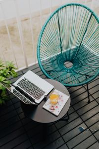 Kaboompics - A stylish garden chair and a small table on the balcony. Macbook laptop, book and a glass of orange juice.