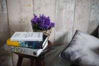 Kaboompics - Books and purple flowers on a wooden stool by the bed