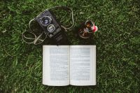 Book on the grass with a vintage camera