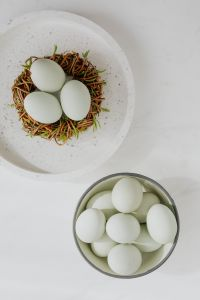 Easter flat lay with green eggs on a white marble