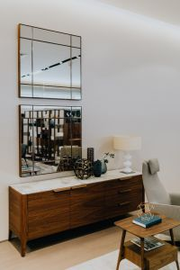 Kaboompics - Wooden and marble commode with big mirrors on a wall, living room