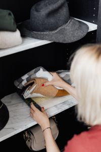 Kaboompics - Woman putting clothes on shelf