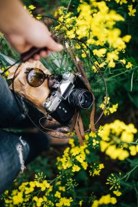 Kaboompics - Woman with vintage camera in the field of blooming rapes