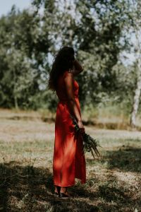 Kaboompics - Woman in a red dress with flowers outdoors