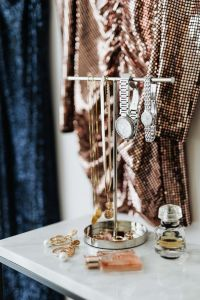 Kaboompics - colored sequin dresses hands on the white wall, marble table with Jewelry
