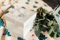 White decorative gift box and eucalyptus twigs on a blanket