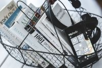 Kaboompics - Black smartphone and headphones and a basket of books