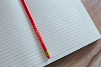 Notebook with a red pencil on a wooden desk