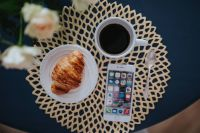 Coffee cup with a croissant and a smartphone on a golden mat