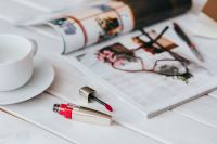 Coffee on table with a magazine and a lipstick