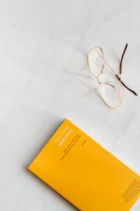 Book and glasses on white marble