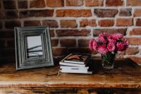 Kaboompics - Photo frame, books and pink flowers in a vase on a wooden commode
