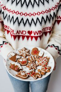 Woman in a white Christmas sweater holds gingerbread cookies on plate