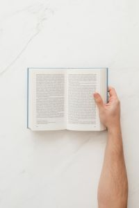 Kaboompics - Hand holding open book on marble table