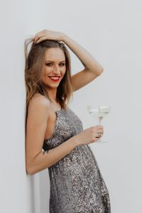 Blond Woman in a Sequin Dress is Holding a Glass of Champagne, White Background