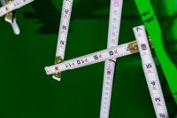 Kaboompics - Extandable wooden ruler on a green background