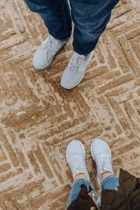 A couple in sports shoes standing on an old brick floor