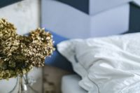 An ornamental golden plant in a jar by the bed with white sheets