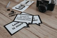 Kaboompics - Little cards with inspirational quotes and a black camera