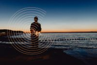 Light painting. The man waving fairy lights at the sea at sunset.