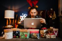 A handsome man with Christmas presents - using MacBook laptop