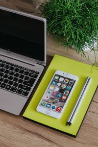 Kaboompics - Silver Acer laptop, a white Apple iPhone, a yellow notebook and a green plant on a wooden desk