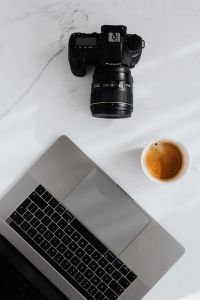 Coffee, laptop and camera on a white marble table
