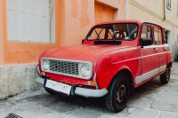An old red Renault 4 car parked on the street in Izola, Slovenia