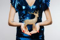 Woman in Blue Dress Holds Gold Reindeer