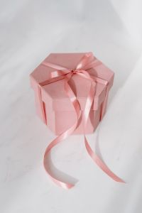 Light pink velvety box with satin ribbon on white marble