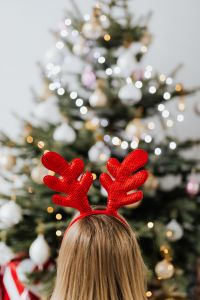 Kaboompics - Woman Wearing Reindeer Horns on Head, Christmas Tree Background