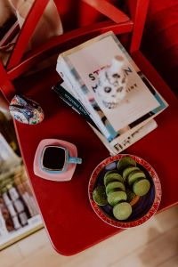 Kaboompics - Coffee, Green Tea Cookies, Books on the Red Chair