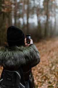 A woman takes a picture with her iPhone X in the autumn forest