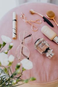 Makeup brushes, eyelash curler & a bottle of perfume on pink velvet