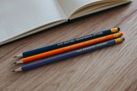 Kaboompics - Notebook with colourful pencils on a wooden desk