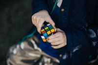 Boy in a blue jacket holding a rubik's cube