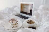 Kaboompics - Macbook, a coffee, a chocolate, a meringue dessert and a notebook in a bed