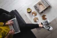 Woman with legs on the coffee table, wearing converse sneakers and working on her laptop
