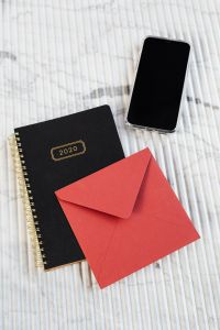 Kaboompics - Red envelope, planner & Iphone on marble