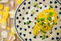 Kaboompics - Yellow rice with greens on a cute plate with blue hearts and a table decorated with flower petals