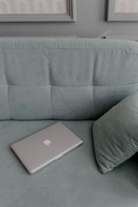 Kaboompics - MacBook laptop lying on mint couch