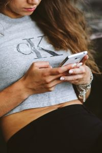 Kaboompics - Young woman holding the white mobile phone