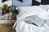 Kaboompics - An ornamental golden plant in a jar by the bed with white sheets and a laptop