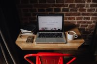 Creatives desk with laptop, camera, journals and books in front of brick wall