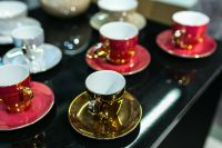 Kaboompics - Red and golden teacups with saucers