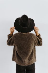 A woman in a brown sweater with a black hat on her head