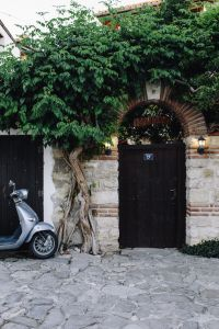 Kaboompics - Scooter parked next to the door on an old street in Nessebar, Bulgaria
