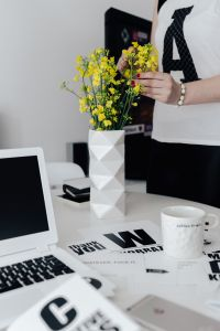 Kaboompics - Woman, yellow flowers in a vase, white laptop, cup, desk