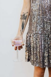Kaboompics - Woman in a Sequin Dress is Holding a Glass of Champagne