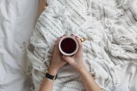 Kaboompics - Soft photo of woman on the bed with the book and cup of tea in hands